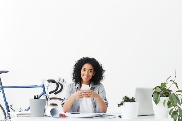 Очаровательная улыбающаяся молодая темнокожая женщина-дизайнер запрашивает такси через онлайн-приложение Бесплатные Фотографии