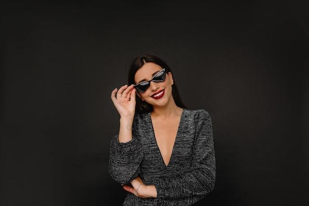 Очаровательная стильная женщина с красными губами держит очки и улыбается Бесплатные Фотографии