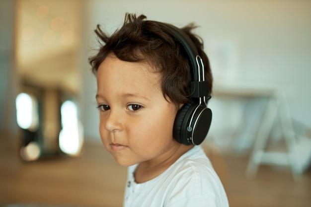 Affascinante ragazzino dolce con i capelli ricci al chiuso con auricolare wireless Foto Gratuite