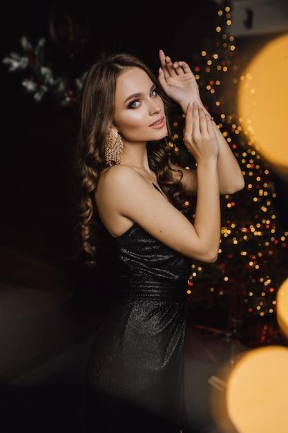 Очаровательная женщина в вечернем пейзаже позирует на дереве кристмас Бесплатные Фотографии