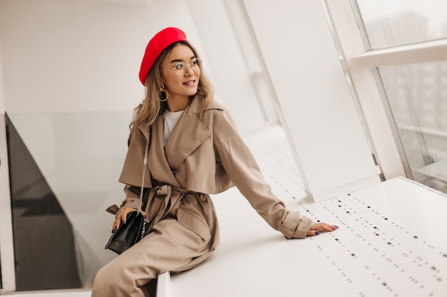 ベージュのコートを着た魅力的な女性が白い窓辺に座って窓の外を見る 無料写真