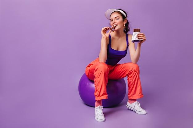 Очаровательная женщина в оранжевых спортивных штанах и фиолетовом топе сидит на фитболе и ест шоколад Бесплатные Фотографии