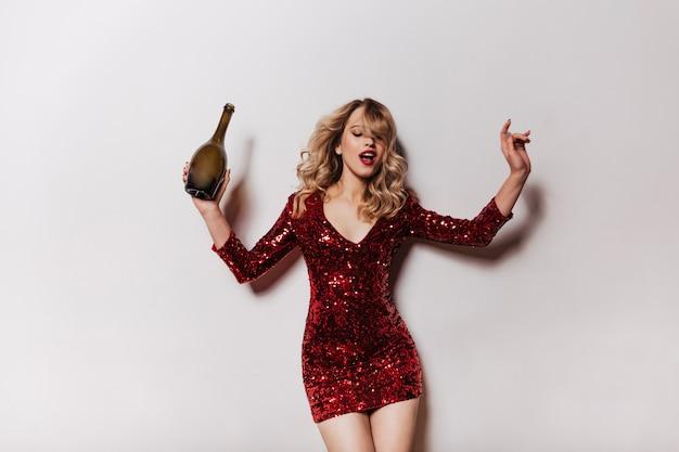Очаровательная женщина в коротком блестящем платье танцует на стене Бесплатные Фотографии