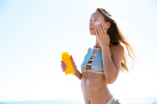Charming woman in stylish swimsuit putting tanning cream on her face Free Photo