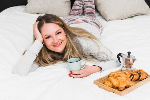 Charming woman lying on bed near breakfast food Free Photo