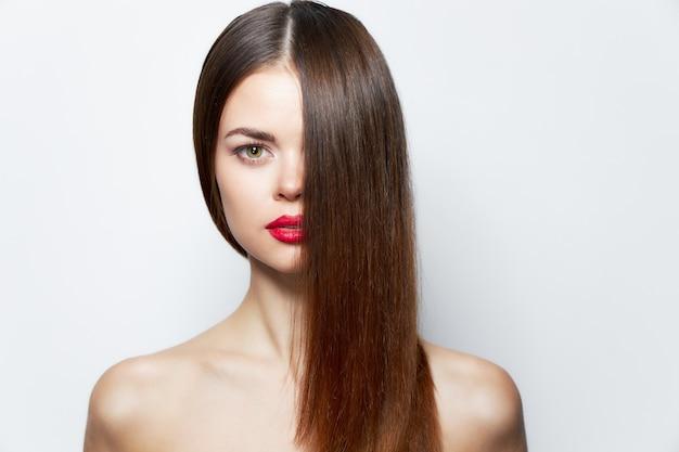 Очаровательная женщина голые плечи красные губы волосы покрывают лицо уход за кожей свет Premium Фотографии