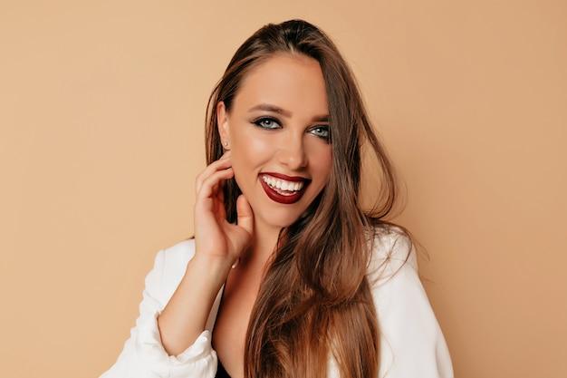 Очаровательная женщина с большими глазами и темными бровями и губами виноградной лозы, улыбающаяся, модель со светлым обнаженным макияжем, бежевая стена Бесплатные Фотографии