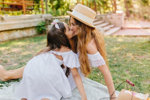 彼女の娘が彼女にキスしている間微笑んでいる巻き毛の長い髪の魅力的な女性。石段のある公園でお母さんと楽しんでいるかわいい女の子の屋外の肖像画。 無料写真