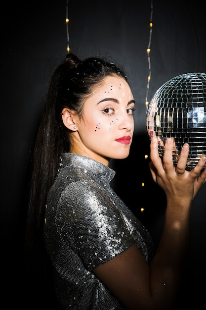 Charming woman with glitters on face holding disco ball Free Photo
