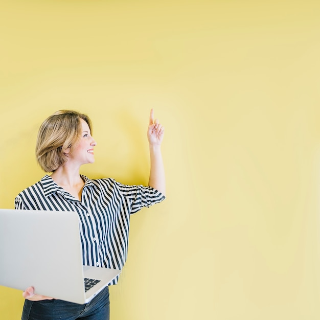 Charming woman with laptop showing up Free Photo