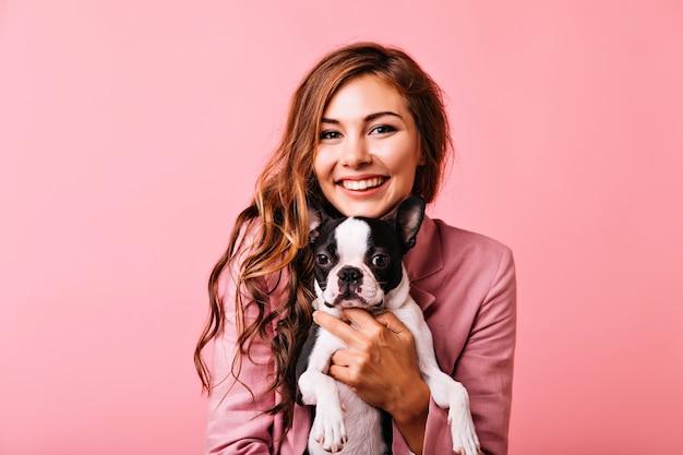 ペットと一緒にポーズをとる光沢のある生姜髪の魅力的な女性。小さな犬を抱いたピンクのジャケットを着た気さくな女の子。 無料写真