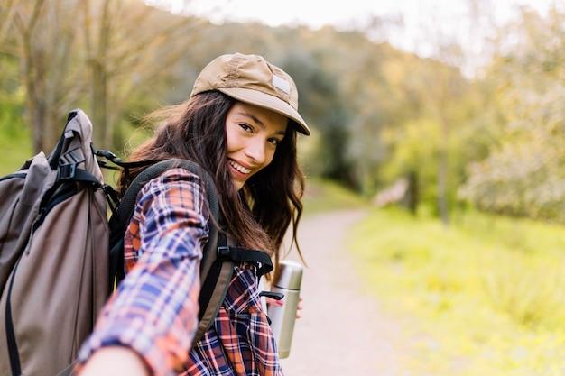 La donna affascinante con thermos che offre il rimorchio cammina con lei Foto Gratuite