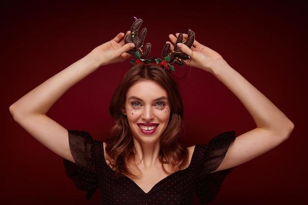 Очаровательная молодая шатенка в праздничной одежде, подняв руки к голове и широко улыбаясь, наслаждаясь рождественской тематической вечеринкой, изолирована Бесплатные Фотографии