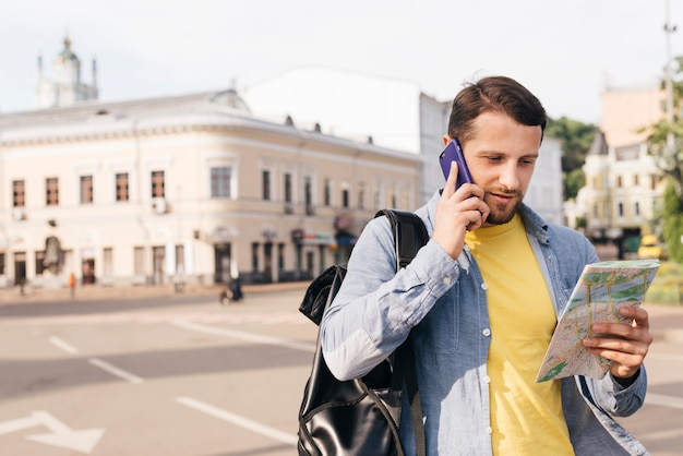 Charming young man looking at map while talking on cell phone on street Free Photo