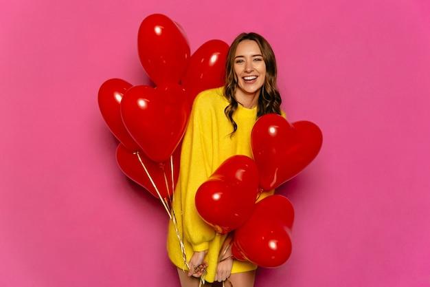 Очаровательная молодая женщина, празднование святого валентина день, проведение красные воздушные шары. Бесплатные Фотографии