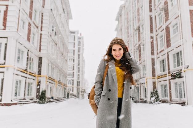 Affascinante giovane donna in cappotto con capelli lunghi del brunette che gode della nevicata in una grande città. emozioni allegre, sorridente, atmosfera natalizia, emozioni positive del viso, clima invernale. posto per il testo. Foto Gratuite