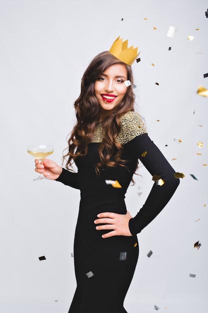 ホワイトスペースで素晴らしい新年のパーティーを祝う豪華な黒のドレスで魅力的な若い女性 無料写真