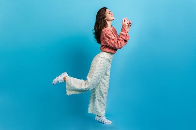 白いズボンの魅力的な若い女性はピンクのカメラで写真を作ります。ピンクのセーターのブルネットのフルレングスの肖像画。 無料写真