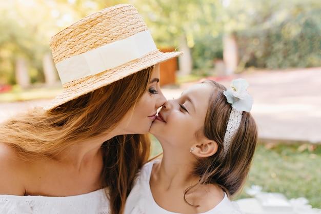 彼女の笑顔の娘を愛してキスする長い黒いまつげを持つ魅力的な若い女性。リボン付きの素敵なママとかわいい長髪の女性の子供のクローズアップの肖像画。 無料写真