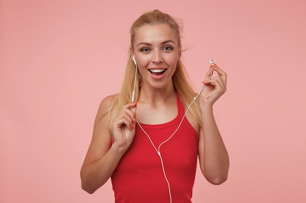 Очаровательная молодая женщина с длинными светлыми волосами в наушниках, радостно смотрящая и держащая наушники, изолированные Бесплатные Фотографии