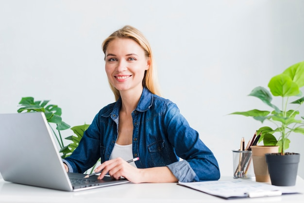 Charming young woman working at laptop in office Free Photo