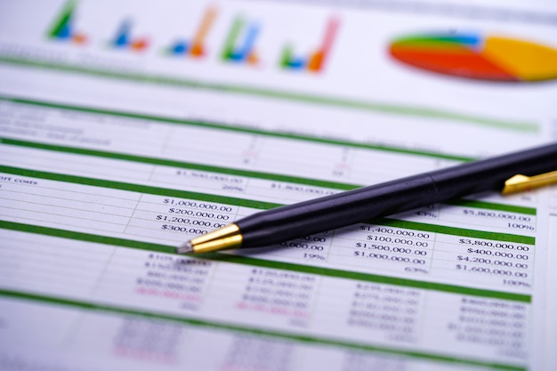 Charts graphs spreadsheet paper with pen. Premium Photo