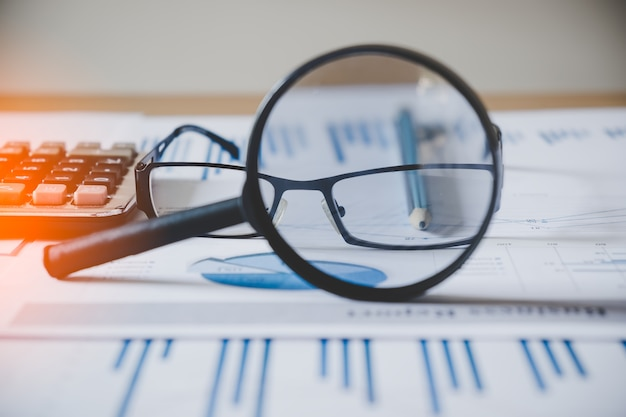 Charts and graphs with magnifying glass and pencil, calculator, clock. reflection light and flare. concept image of data gathering and statistical working. Premium Photo