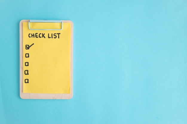 check list paper on wooden clipboard over the blue background photo