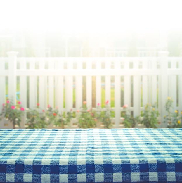 白いフェンスと庭の背景のぼかしに市松模様のテーブルクロス。 Premium写真