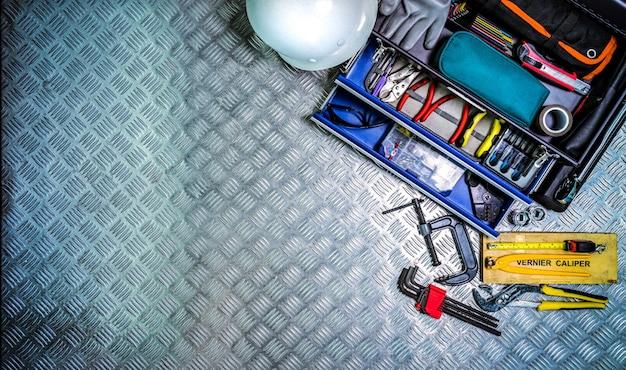 Взгляд сверху коробки и шлема инструментов на checkered предпосылке плиты в мастерской. Premium Фотографии