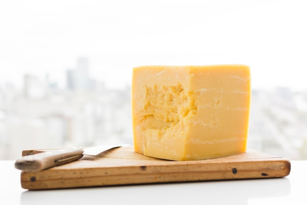 Cheddar cheese cube with knife on chopping board over the desk Free Photo