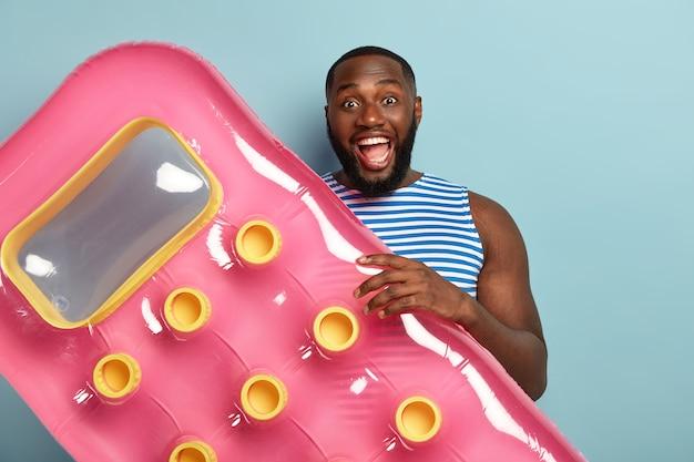 陽気な暗い肌の男性の行楽客はピンクの膨らんだマットレスを保持し、水泳の準備をし、楽しく笑います 無料写真