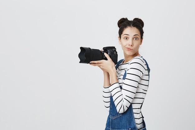 写真を撮る生意気なかわいい女の子、女性写真家またはパパラッチ保持カメラ 無料写真