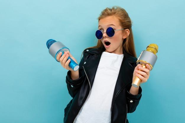 水色の背景に2つのマイクで歌うサングラスの生意気なヨーロッパの女の子。 Premium写真