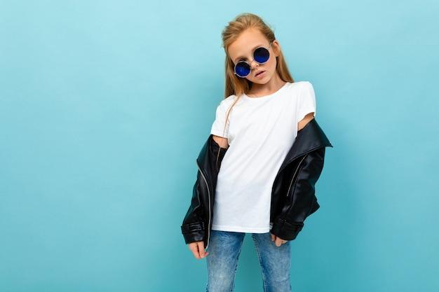 水色の背景にモックアップとタンクトップとサングラスで生意気なヨーロッパの女の子 Premium写真