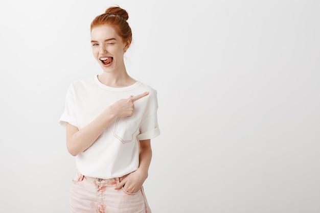 生意気な笑顔の赤毛の女の子ウインクと右の人差し指 無料写真