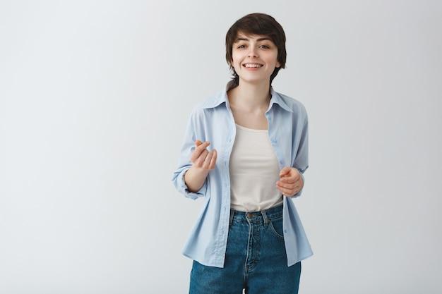 短い髪のポインティング、会話をしている生意気な笑顔の女性 無料写真