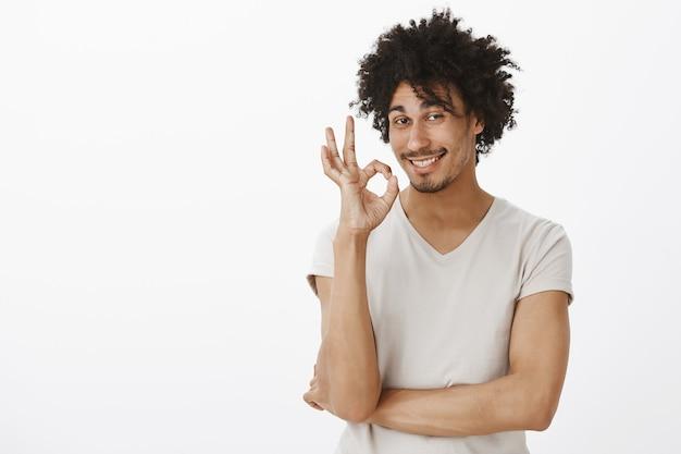 生意気な笑顔の若い男は問題ないと言っています、よくやった。男は良い選択を賞賛し、大丈夫なジェスチャーを示して満足 無料写真