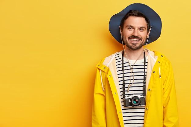陽気なアクティブな若い男性旅行者は、広く笑顔で、好きな趣味のための暇な時間を楽しんで、レトロなカメラで写真を作り、カジュアルなレインコートと帽子を着て、遠征や探検を楽しんでいます。 無料写真