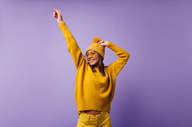 La ragazza adorabile allegra muove le sue mani. ritratto di studente attivo in jeans luminosi Foto Gratuite