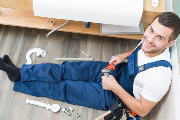 Cheerful adult plumber sitting in bathroom Free Photo