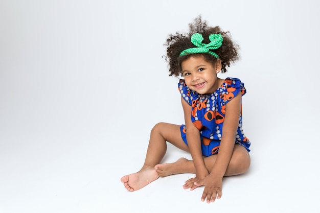 Cheerful african american child in blue and orange colored dress Premium Photo