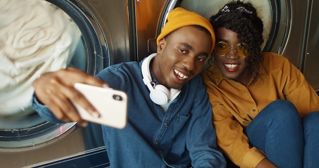 陽気なアフリカ系アメリカ人カップルがランドリーサービスでselfie写真を撮っている間、スマートフォンのカメラに笑顔します。幸せな魅力的な若い男と女が公共のコインランドリーで電話で写真を作ります。 Premium写真