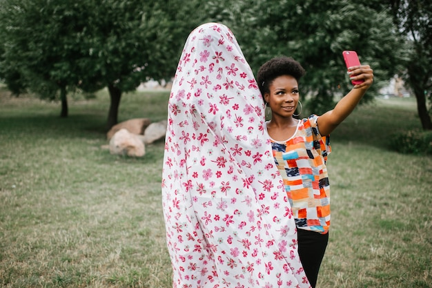 Cheerful african american girl standing with a person in ghost costume outdoor and taking selfie. halloween party concept. Premium Photo