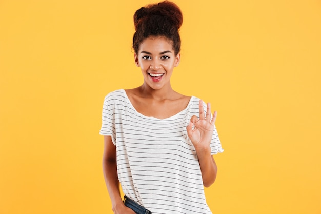 Cheerful african lady with curly hair showing ok gesture isolated Free Photo