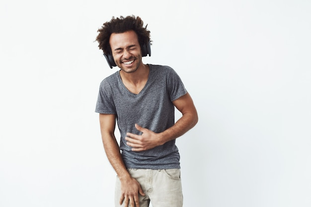 Cheerful african man in headphones laughing closed eyes. Free Photo
