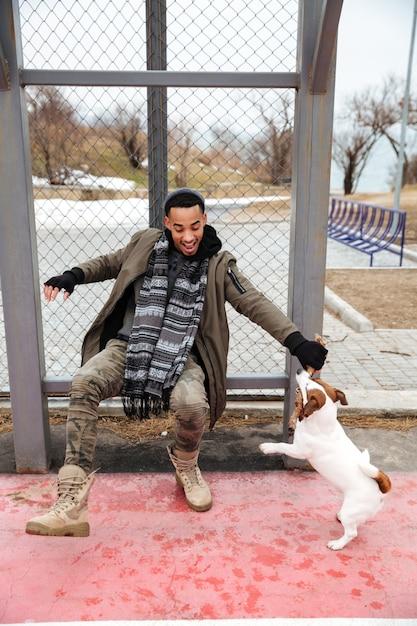 Веселый африканский человек играет с собакой и смеется на открытом воздухе Бесплатные Фотографии