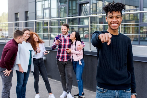 Cheerful african man pointing towards camera standing in front of his friends Free Photo