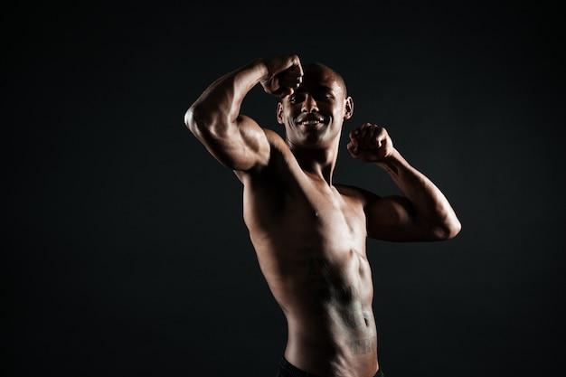 Веселый афроамериканский спортивный человек, показывающий его бицепс Бесплатные Фотографии