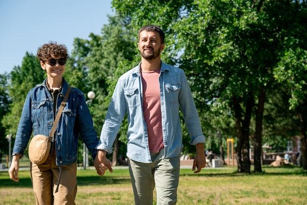 Веселая и ласковая молодая пара в брюках и джинсовых куртках гуляет в общественном парке в солнечный день Premium Фотографии